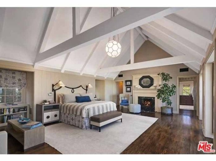 the-bedroom-features-a-dramatic-cathedral-ceiling